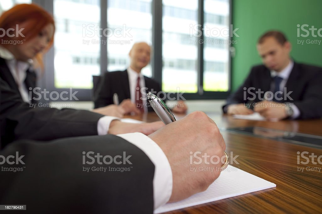 writing hand of businessman in meeting royalty-free stock photo