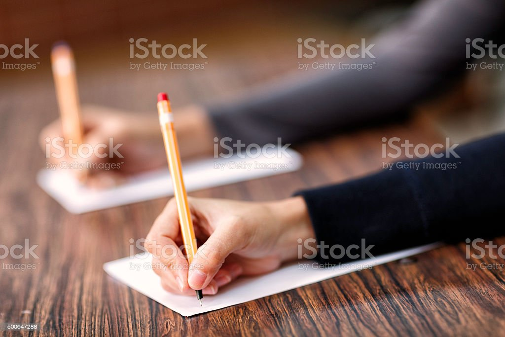 Writing hands on a desk in classroom stock photo