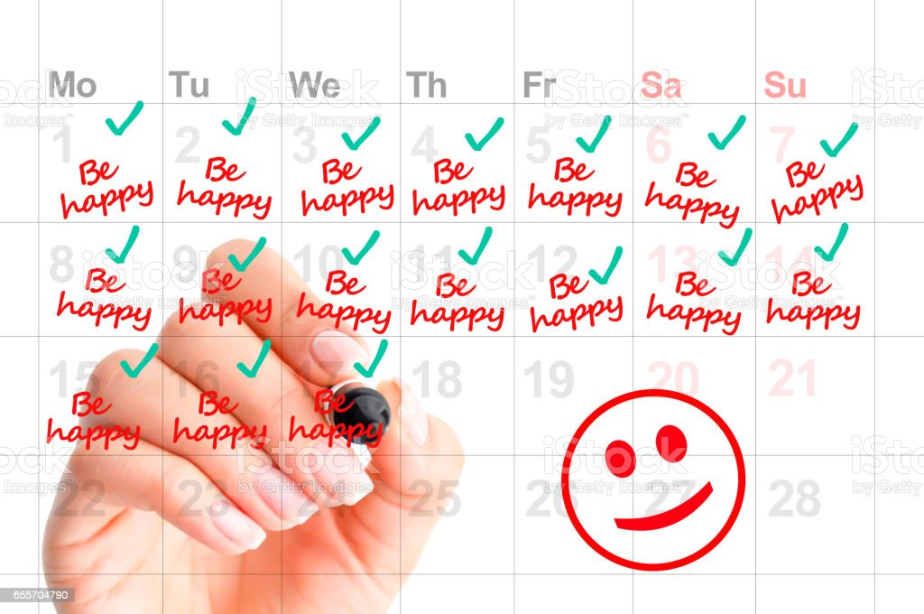 Writing in a calendar to be happy and to smile more as a wish for next year resolution stock photo