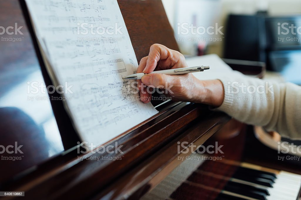 writing notes on sheet music stock photo