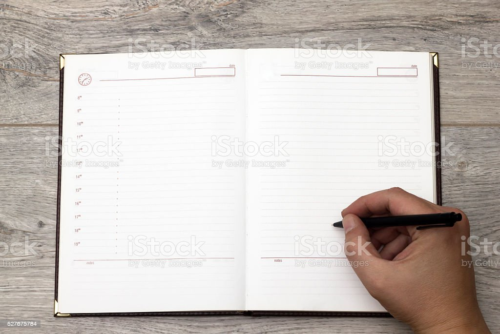 Writing on blank paper personal organizer. Directly above view. stock photo
