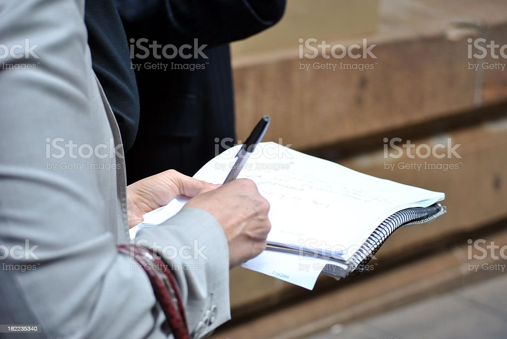 Writing on the journal for a report stock photo