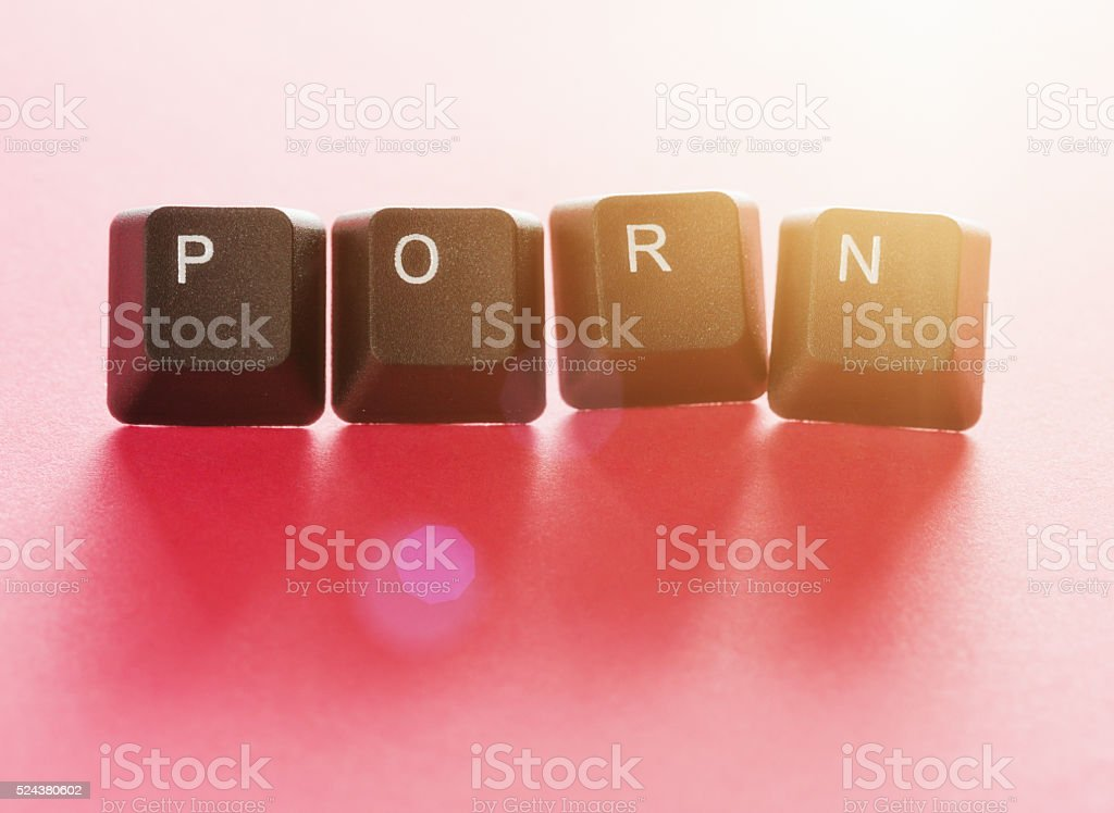 'PORN' written in computer keys on shaded red background: Cybersex! stock photo