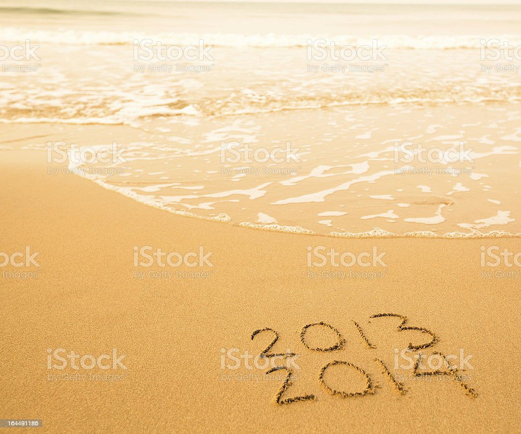 2013 - 2014 written in sand on beach texture stock photo