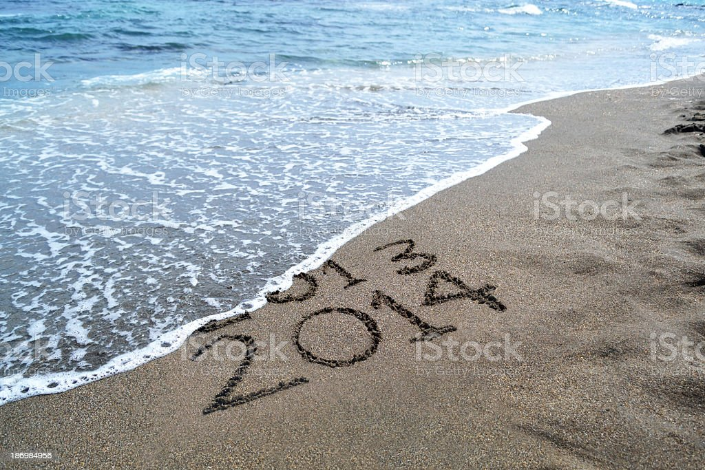 2013 2014 written in the sand, getting washed out by ocean stock photo