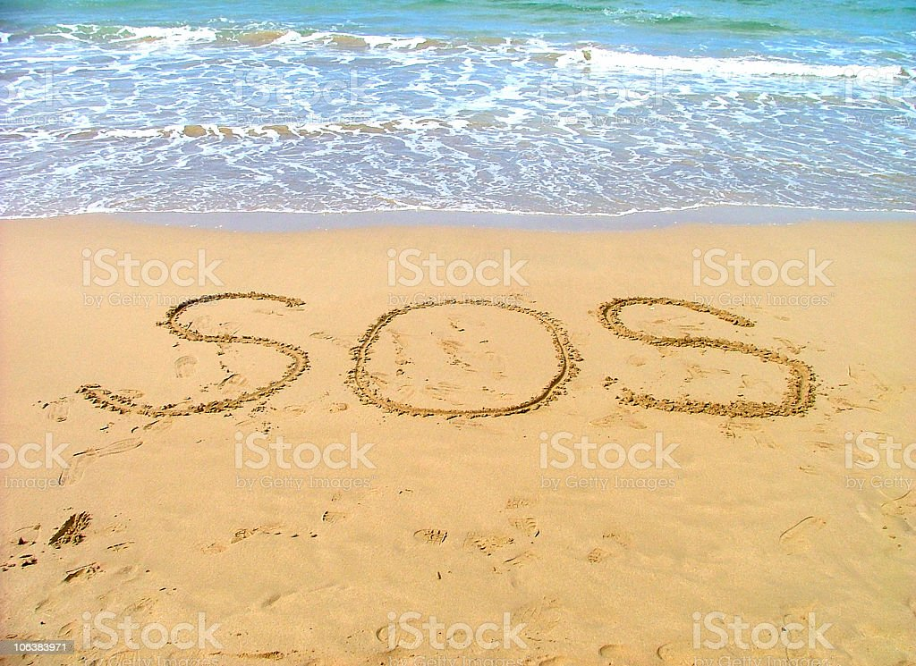 SOS written in the sand on a beach stock photo