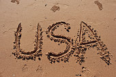 'USA' written in the sand on the beach