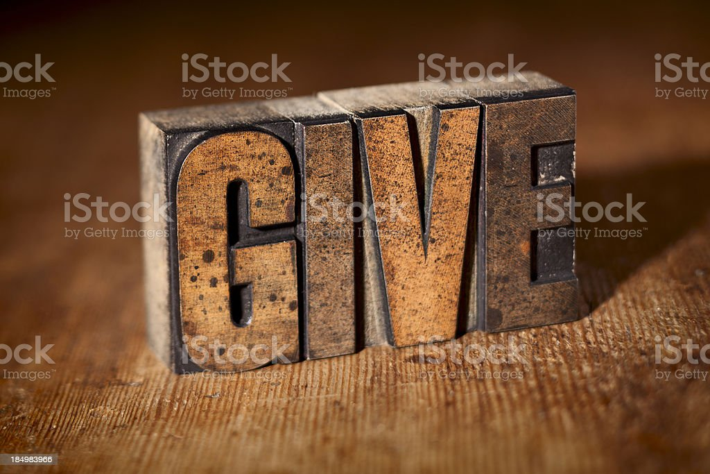 GIVE written in wooden letterpress on wood background royalty-free stock photo
