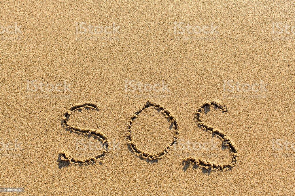 SOS - written manually on the texture of sea sand. stock photo