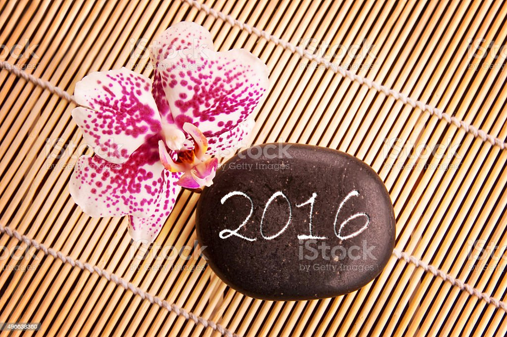 2016 written on a black pebble with pink orchid stock photo