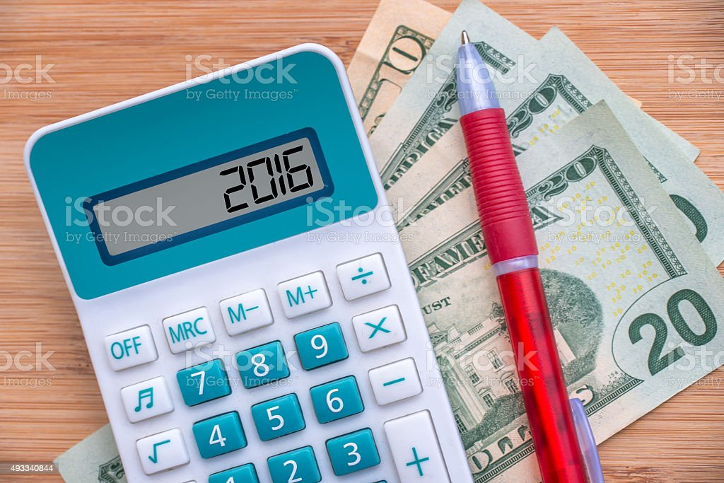 2016, written on a calculator and dollars banknotes on wood stock photo