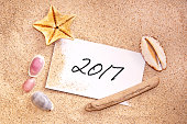 2017, written on a note in the sand with seashells