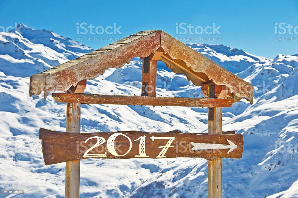 2017 written on a wooden direction sign, snowy mountain stock photo