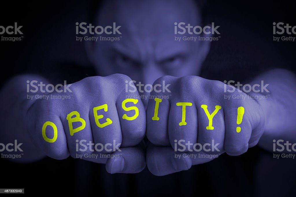 OBESITY written on an angry man fists royalty-free stock photo