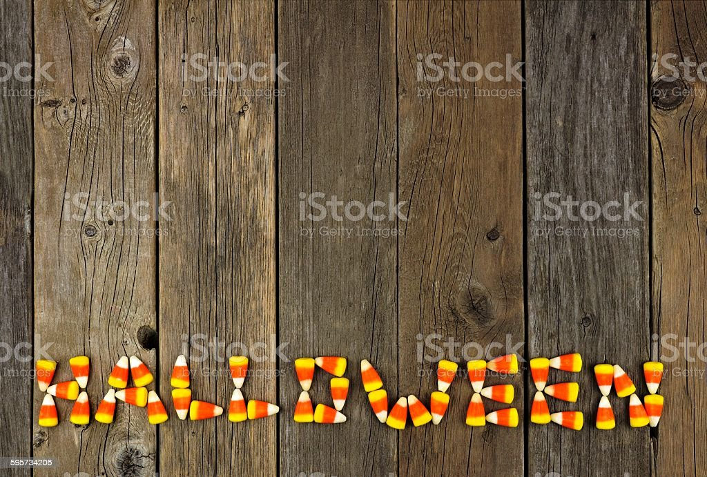 HALLOWEEN written with candy corn over rustic wood stock photo
