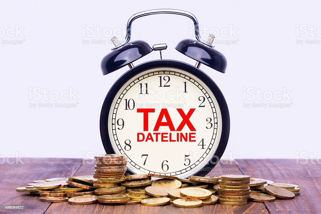Written word Tax Dateline on a clock with gold coins stock photo