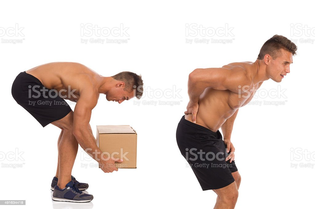 Wrong way of picking up weight. Backache. stock photo