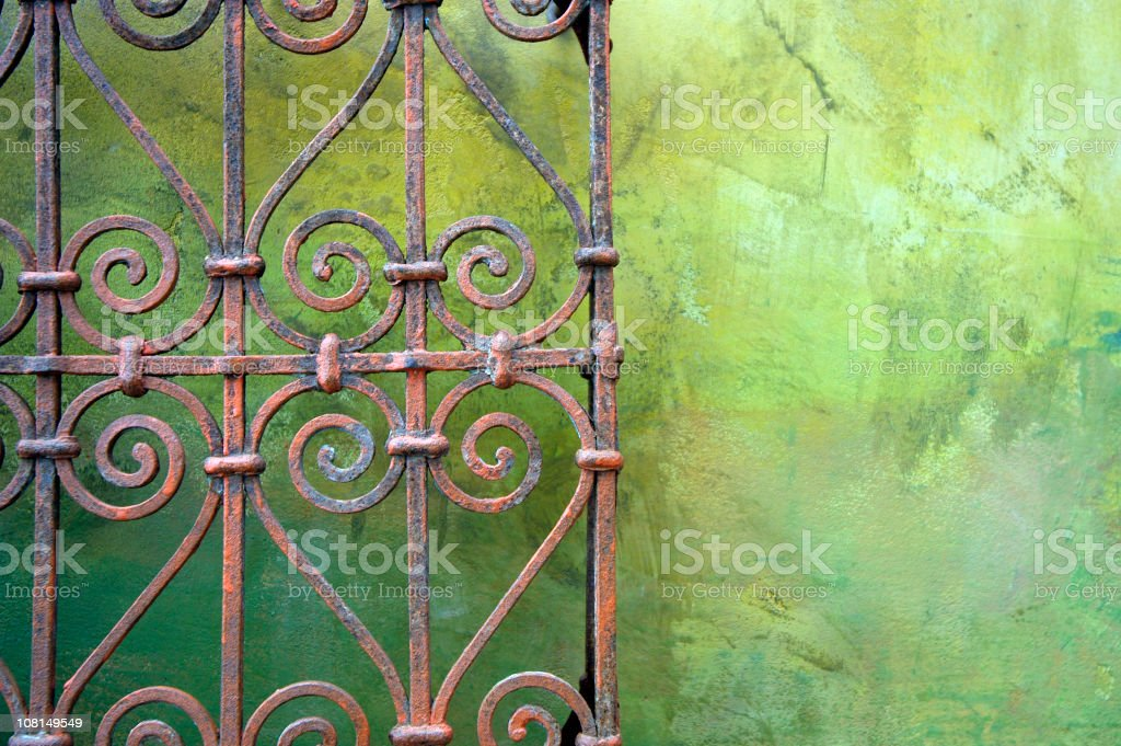 Wrought iron fence against green wall royalty-free stock photo