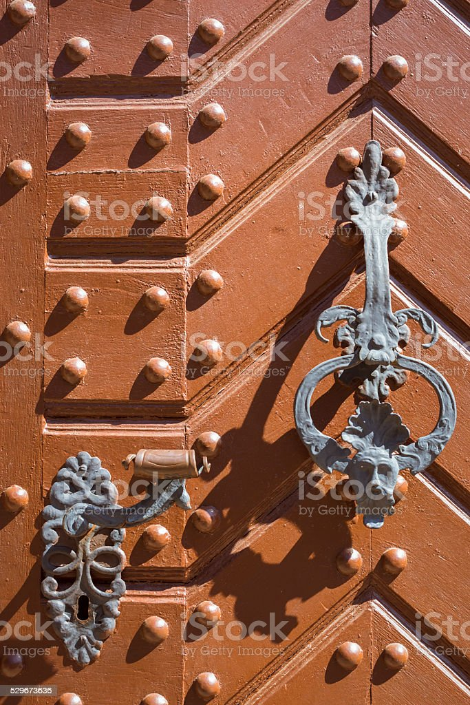 Wrought-iron bell and handle on orange door with metal rivets stock photo