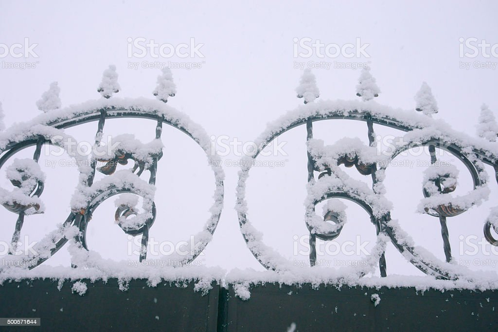 wrought-iron gate in the snow stock photo
