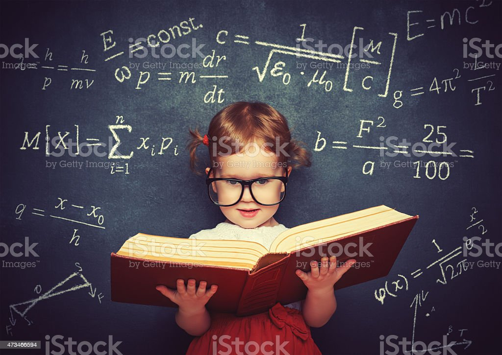 wunderkind little girl schoolgirl with a book from the blackboar stock photo