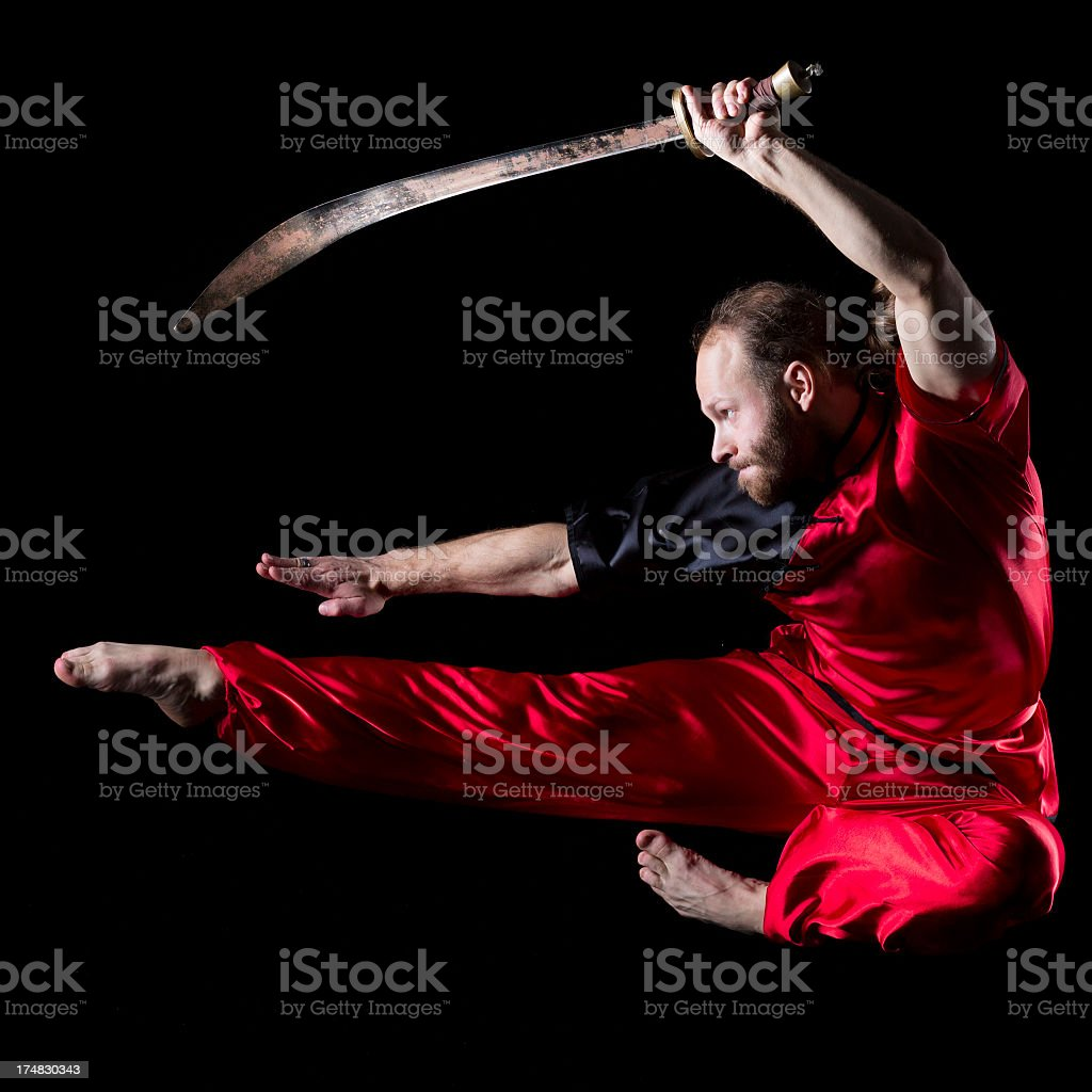 Wushu fighting position with Dao sword in midair stock photo