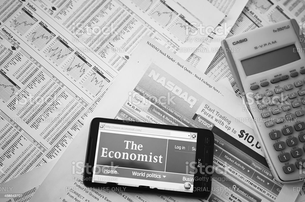 www.economist.com on HTC smart phone and financial newspaper stock photo