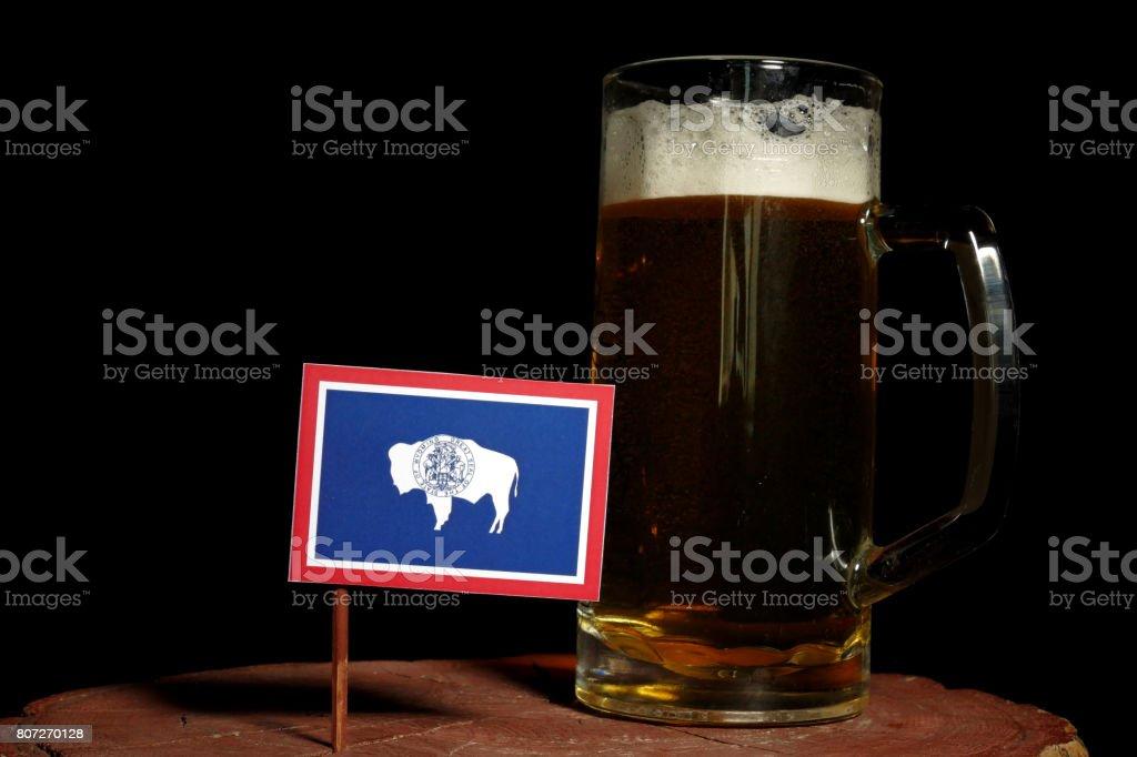 Wyoming flag with beer mug isolated on black background stock photo