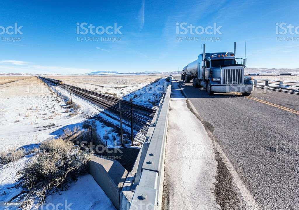 Wyoming Winter Converging Tanker Trailer Truck and Freight Train stock photo