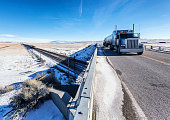 Wyoming Winter Converging Tanker Trailer Truck and Freight Train