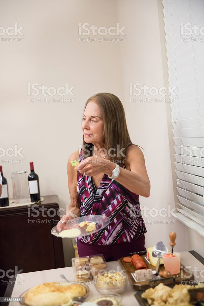 X-Caucasian senior woman eating at party buffet table stock photo