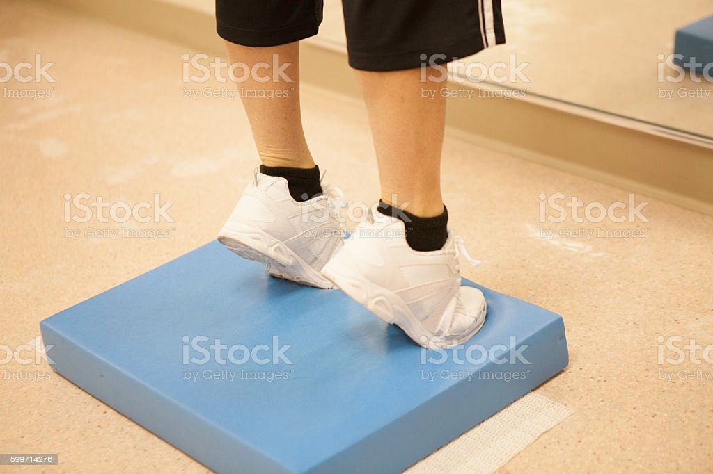 X-Woman doing heel lifts to strengthen her calf muscles. stock photo