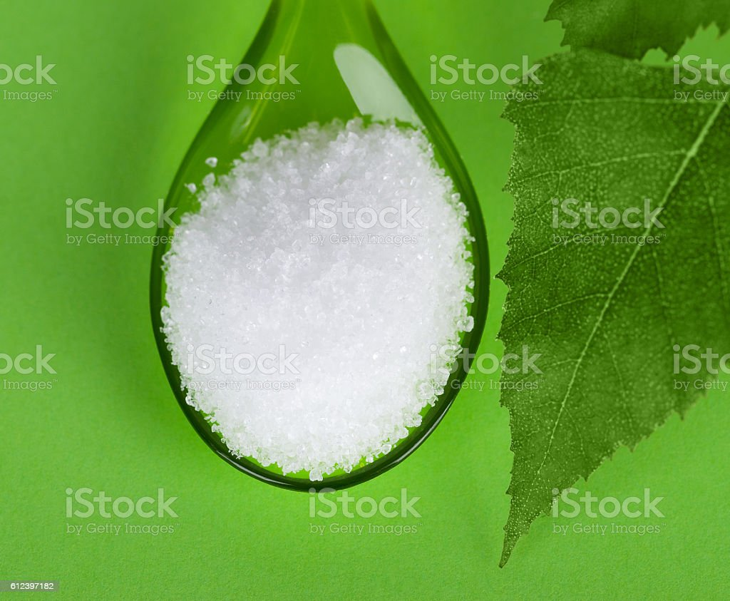Xylitol birch sugar on green plastic spoon stock photo