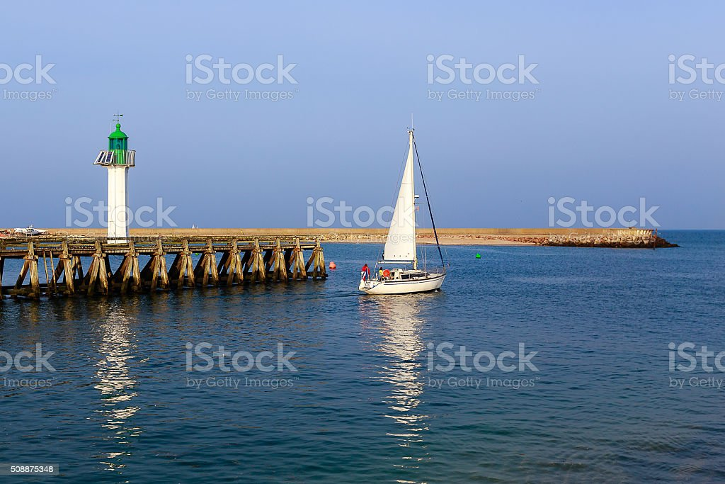 Yacht and lighthouse in the city of Deauville, Normandy, France stock photo