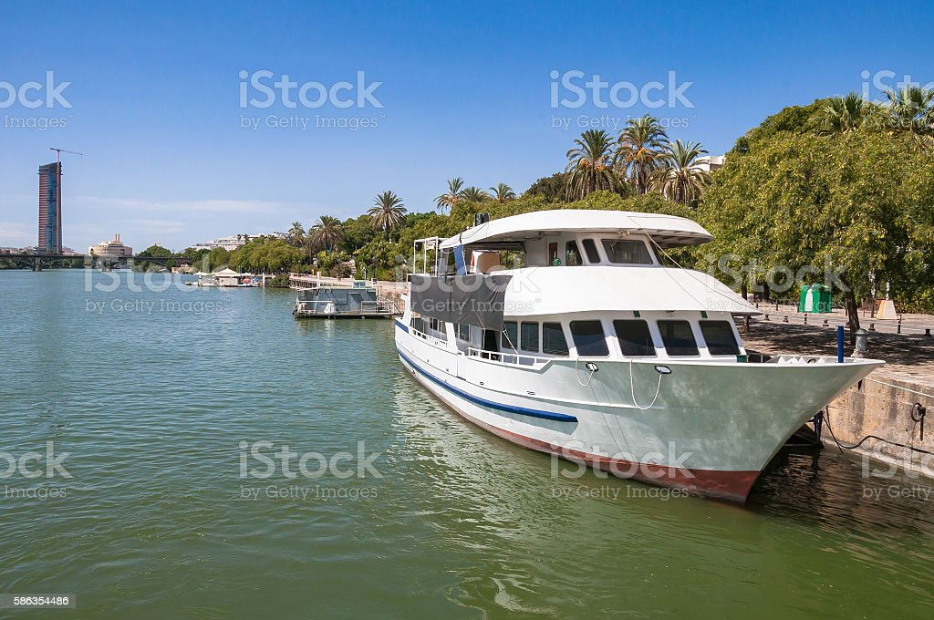 Yacht at a pier on Guadalquivir River in Seville stock photo