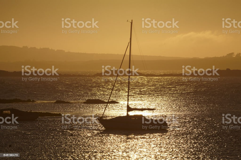 Yacht in evening, Rhosneigr, Anglesey, Wales. stock photo