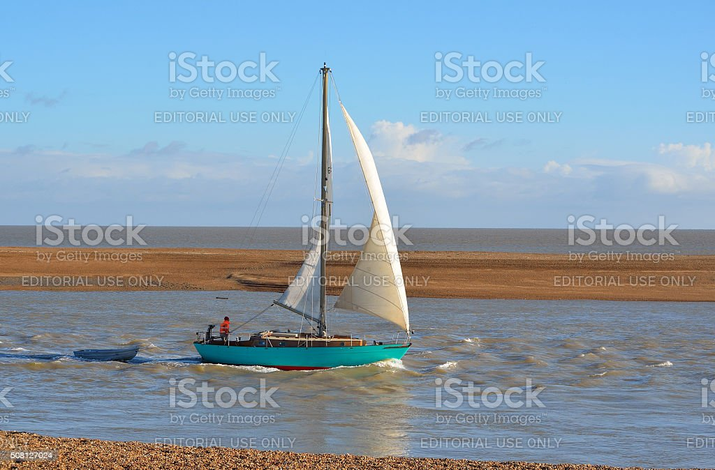 Yacht leaving Felixstowe Ferry at the mouth of the river Deben. stock photo