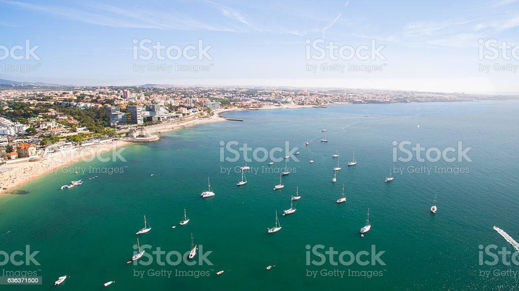 yacht near beautiful beach and marina of Cascais Portugal aerial stock photo