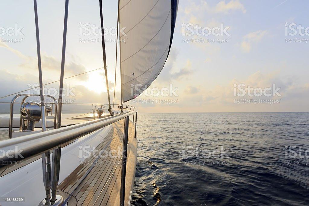 Yacht sailing at sunset stock photo