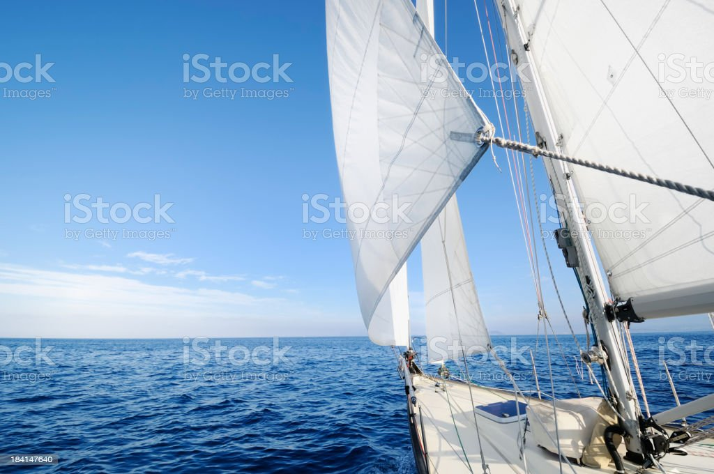 A yacht sailing in the open sea on a bright day stock photo