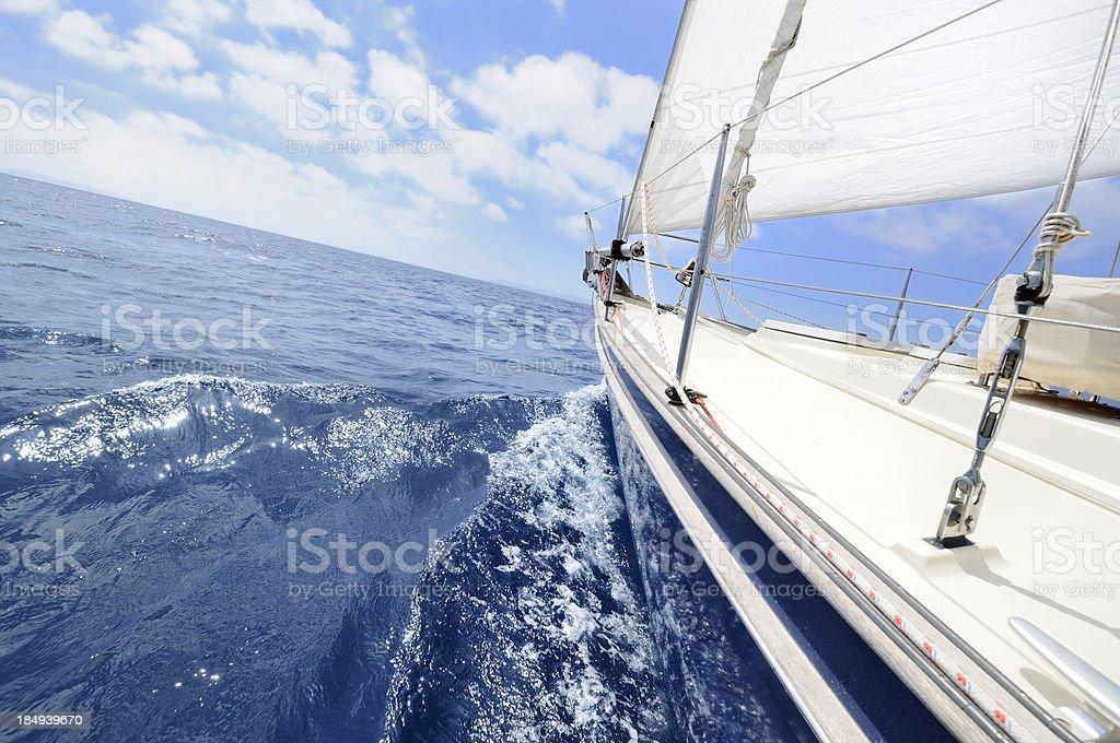 Yacht sailing towards the horizon on summer day royalty-free stock photo