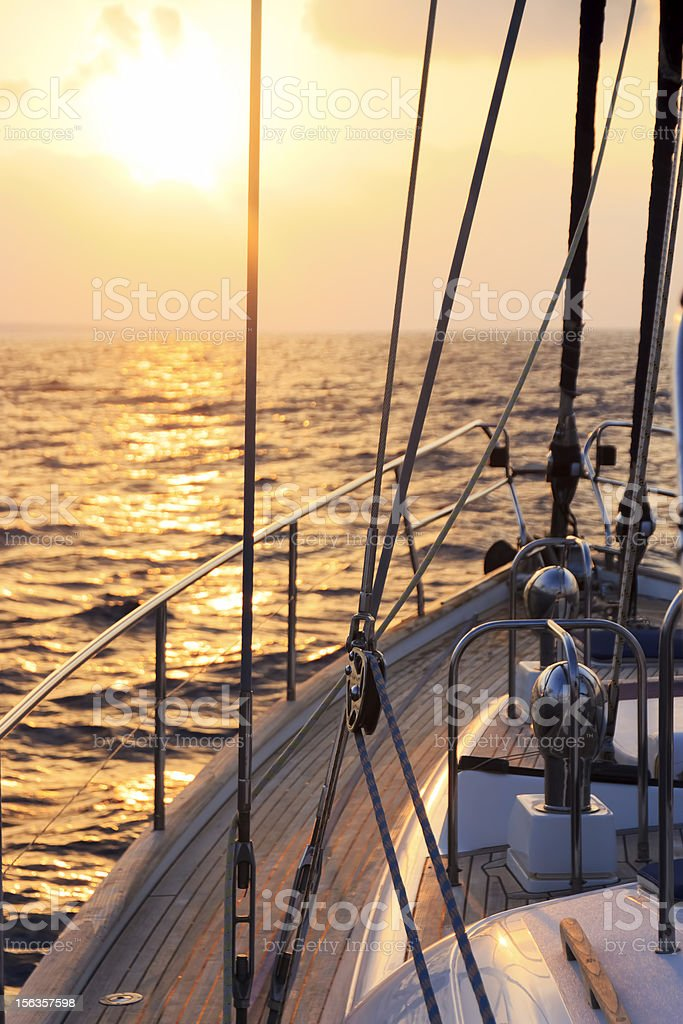 Yacht sailing towards the sunset royalty-free stock photo