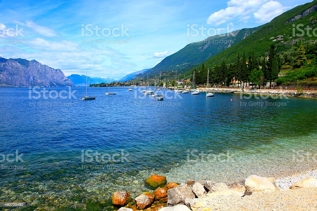 Yacht ship and Italian turquoise translucent Lake Garda paradise, Malcesine stock photo
