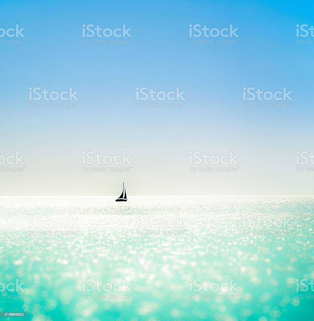 Yacht silhouetted on a sparkling sea stock photo