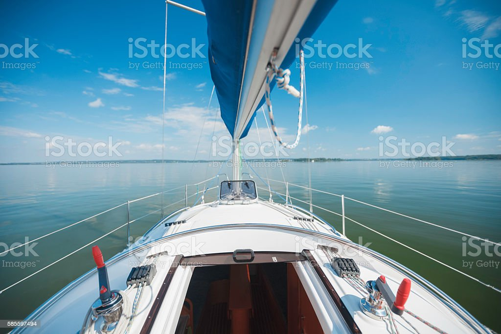 Yacht with a sail floating on the lake. stock photo
