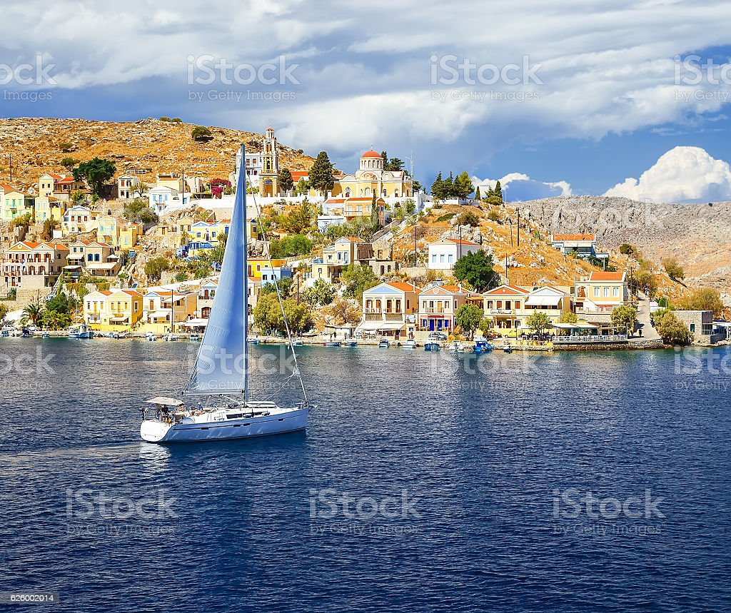 yacht with full sails against beautiful buildings of Symi, Greece stock photo