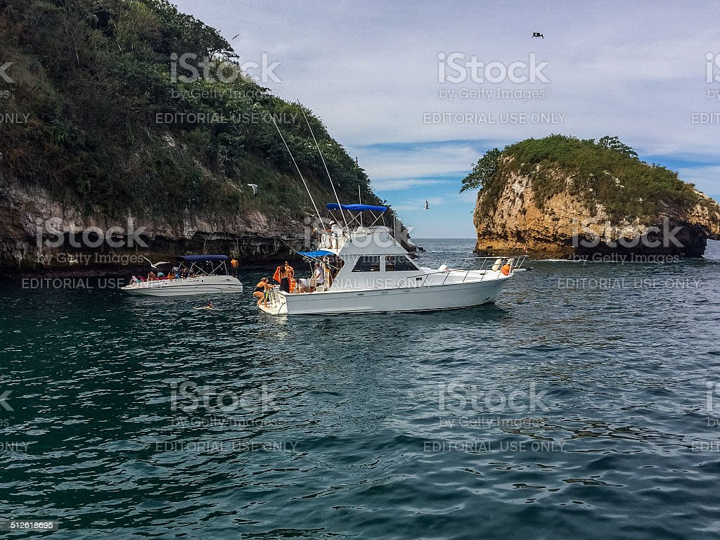 Yacht with tourists visiting ocean rocks in Puerto Vallarta, Mexico stock photo