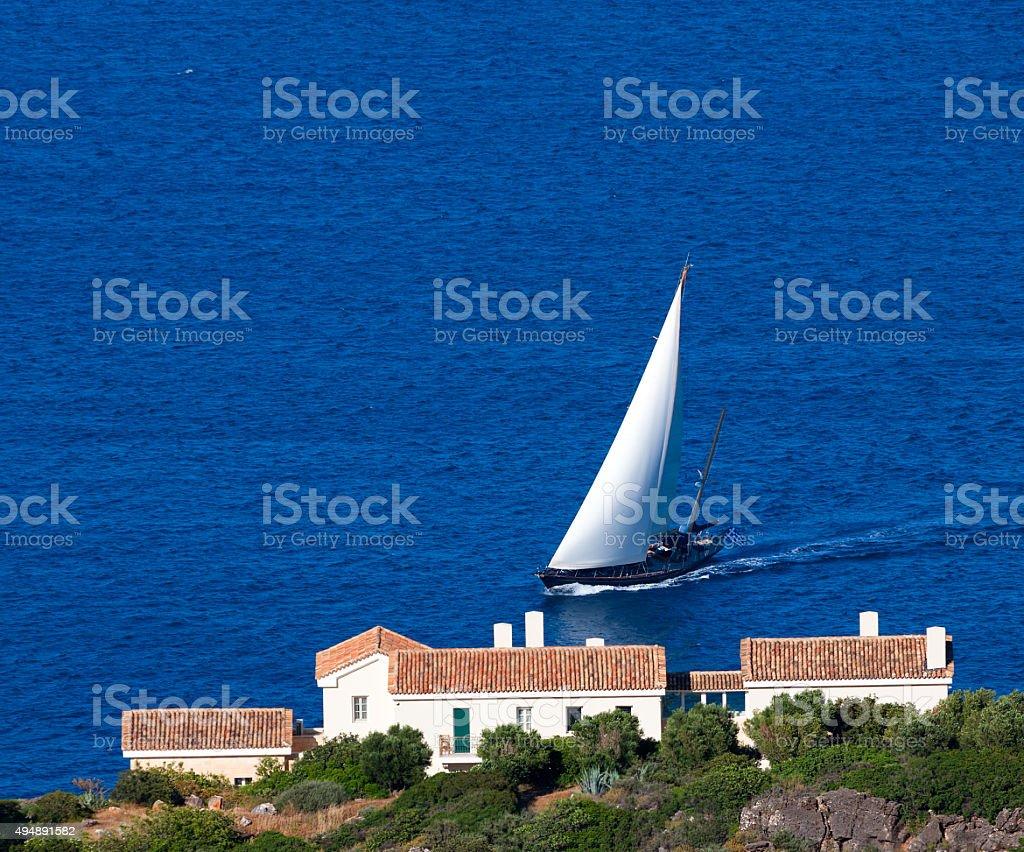 Yacht with white sail swim to the shore of Crete. stock photo