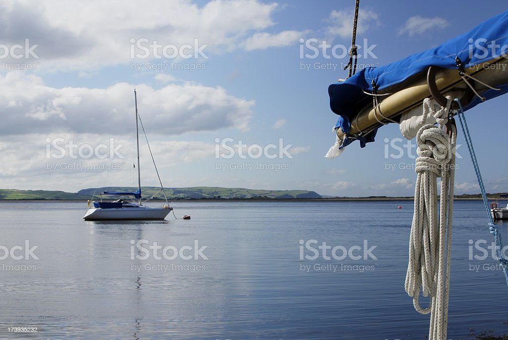 Yacht's Boom and a moored yacht on water royalty-free stock photo