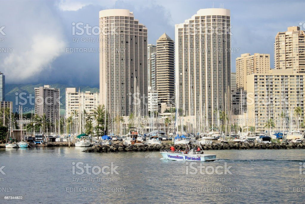 Yachts docked at Ala Wai Boat Harbor in the Kahanamoku Lagoon against cityscape of Ala Moana. stock photo